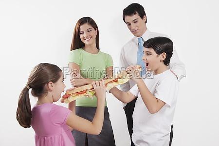 boy sharing a submarine sandwich with