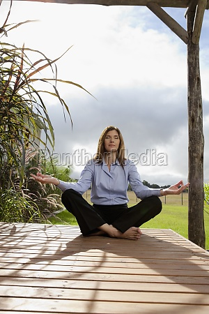 businesswoman meditating in a park