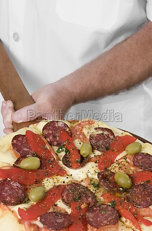 chef holding a pizza on a