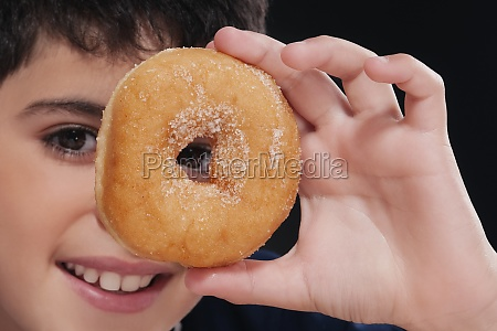 boy holding a donut in front