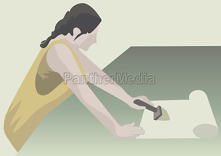 woman applying glue on wallpaper with