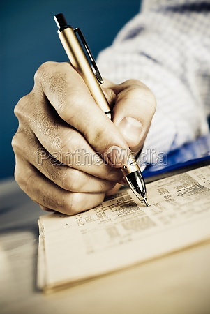 personZs hand marking on financial newspaper