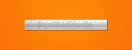 metal ruler isolated on orange background