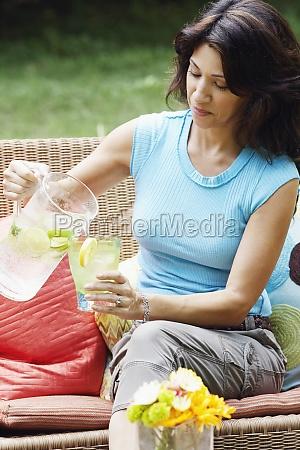mature woman pouring lemonade into a