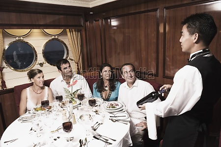 waiter serving wine bottle to two