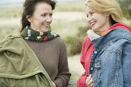 two mature women gossiping and smiling