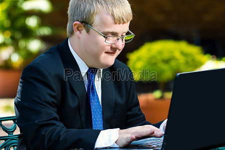 young handicapped businessman working on laptop