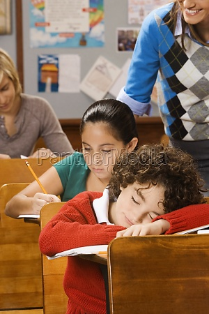 students studying with a schoolboy sleeping