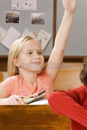 schoolgirl raising her hand in a