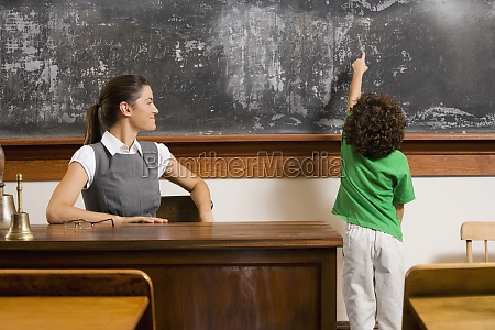 schoolboy pointing at a blackboard with