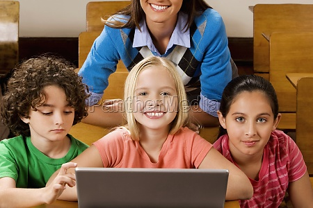 students with their teacher using a