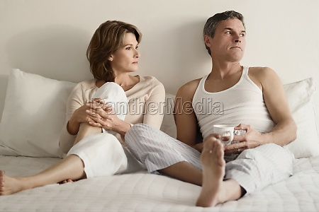couple looking serious on the bed
