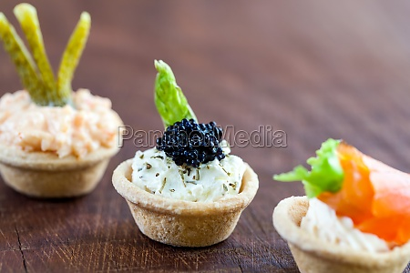 mini savory tartlets on wooden surface
