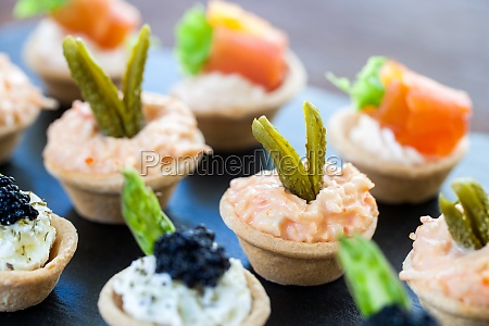 multiple mini pastry tartlets with seafood
