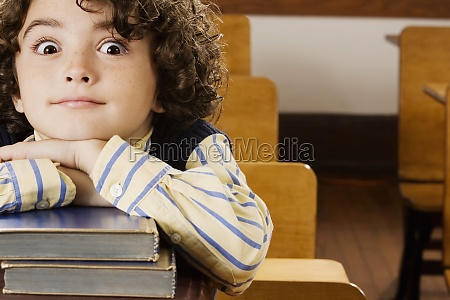 schoolboy sitting with books in a