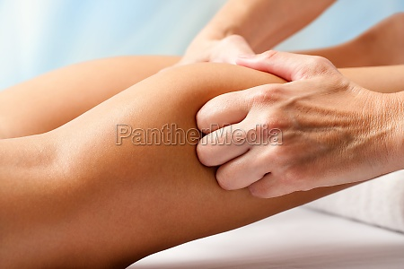 physiotherapist hands massaging calf muscle