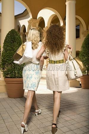 rear view of women holding shopping