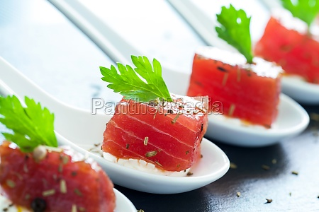 appetizing tuna morsel on ceramic spoons