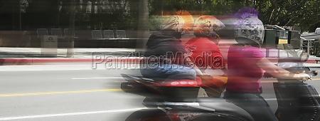 three people racing on motor cycles