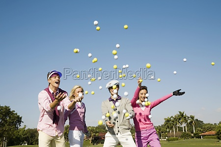 four friends throwing golf balls in