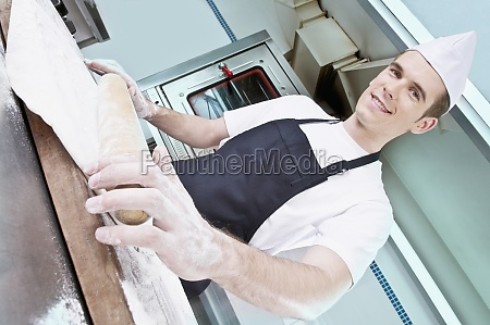 chef rolling dough with a rolling