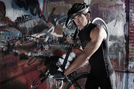 man carrying a bicycle on his
