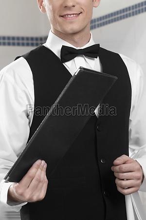 waiter holding menu in a restaurant