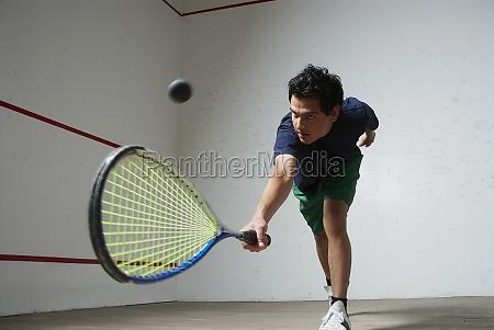 young man playing squash