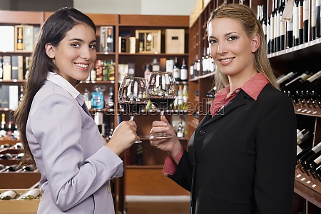two businesswomen toasting with wine in