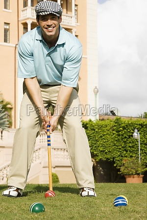 man smiling and playing croquet in