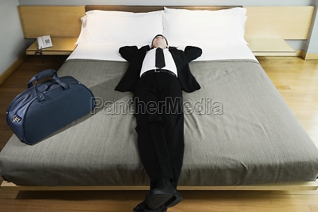 businessman napping on the bed