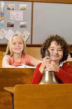 schoolboy holding a bell with a
