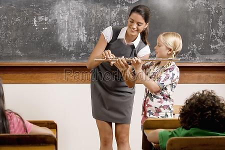teacher helping a schoolgirl playing a
