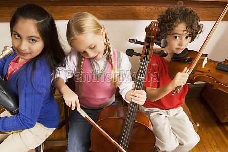three students playing musical instruments in