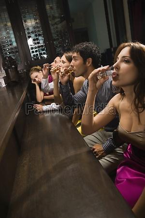 five friends sitting at a bar