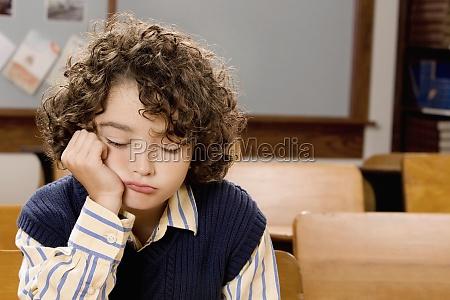 sad schoolboy sitting in a classroom