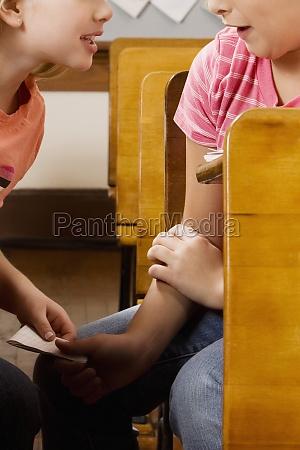 two schoolgirls passing note during exam