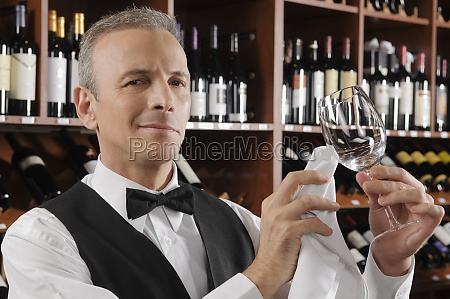 waiter cleaning a wine glass in