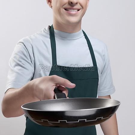 man holding a frying pan