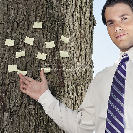 businessman showing adhesive notes stuck on