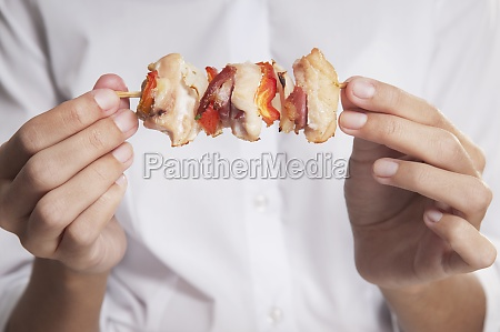 woman holding a shish kebab