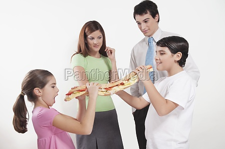 two children eating a submarine sandwich