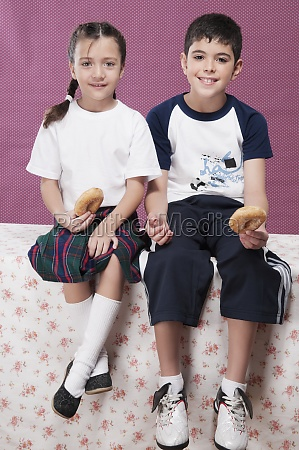 boy and his sister holding donuts