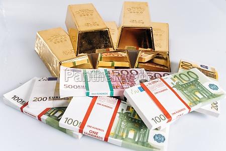 gold bullions at euro banknotes closeup