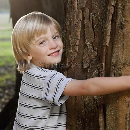 boy hugging a tree in a