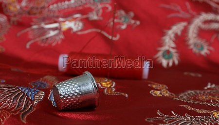 thimble and thread on asian red