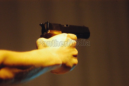 person aiming with a pistol