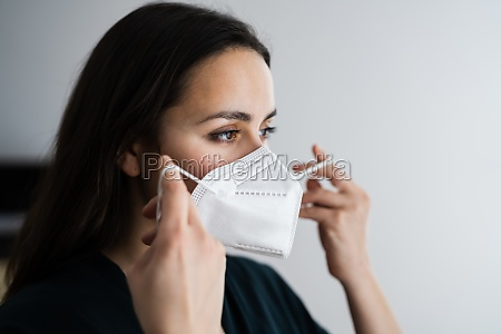 woman putting on medical face mask