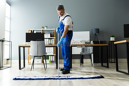 male janitor mopping floor in face