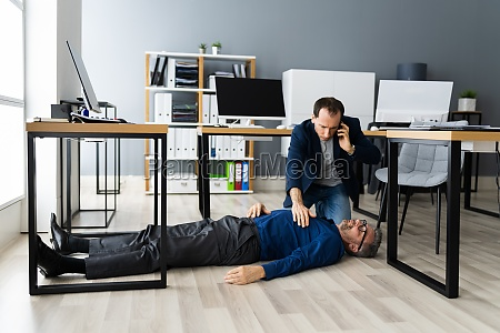 helping aged fainted man on office
